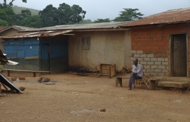 Man sitting outside a house in Conakry, Guinea